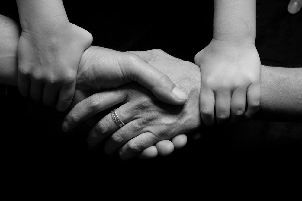 People holding hands to show how family support matters.
