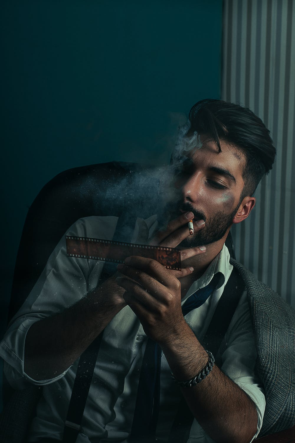 A young man smoking in dark room.